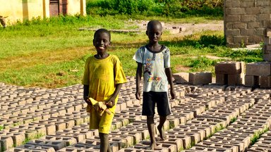 Local children walk across bricks made for the construction of the wall .jpg