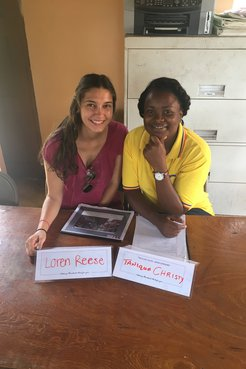 Loren Reese and a Jamaican community counterpart pose with their name plates.