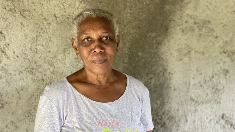A older, black Jamaican woman stands in front of a grey wall and smiles.