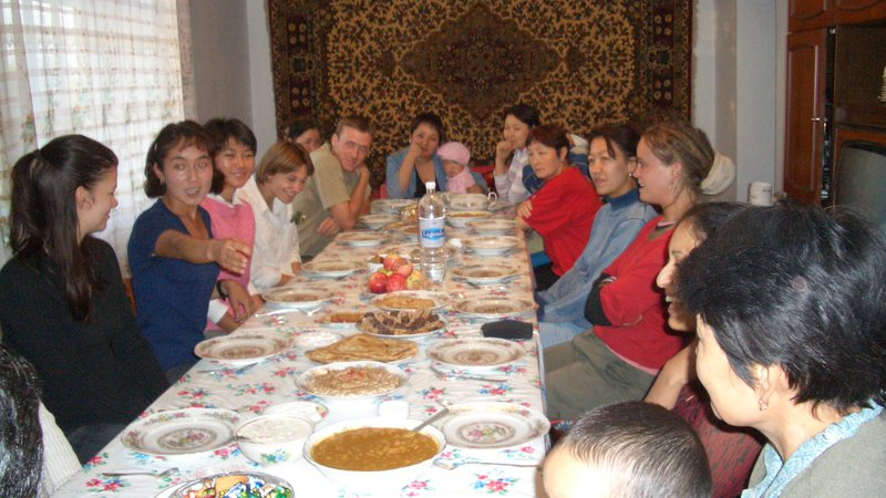 Mahima's family and host community sit and eat a traditional Indian meal together in Kyrgyzstan.
