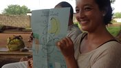 A female Volunteer sits outside and hold up a drawing of nutritious foods and moringa