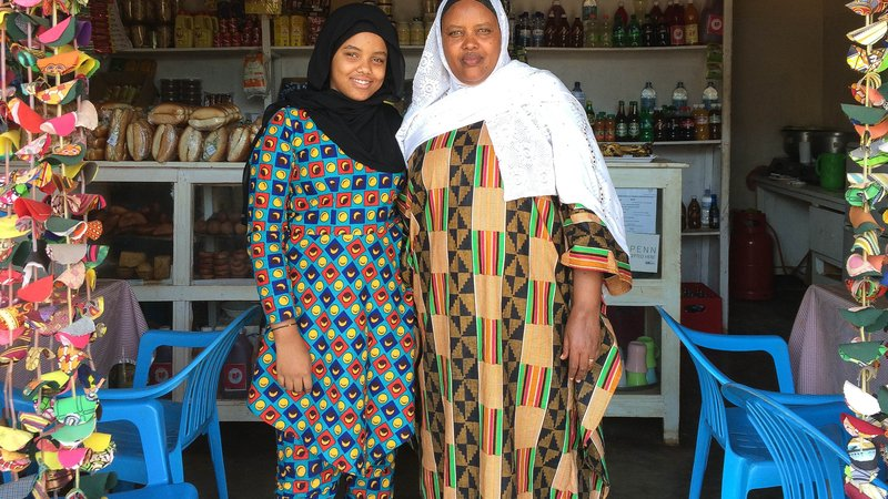 Jamila and Tata stand in their shop side by side for a photo