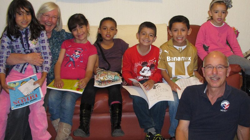 Mary and John engage children with coloring books about plants and wildlife.