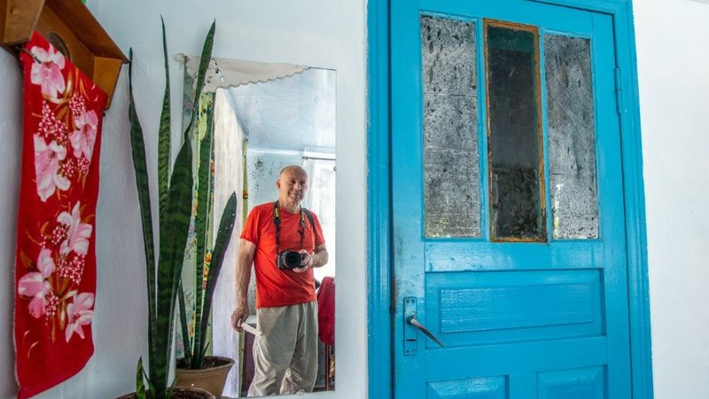 A man stands with his camera around his neck in front of a mirror. To the right is a bright blue door, to the left is a plant