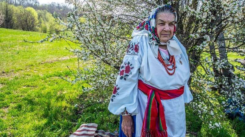 An older Ukrainian woman stands in traditional attire amid a green field and blooming tree.