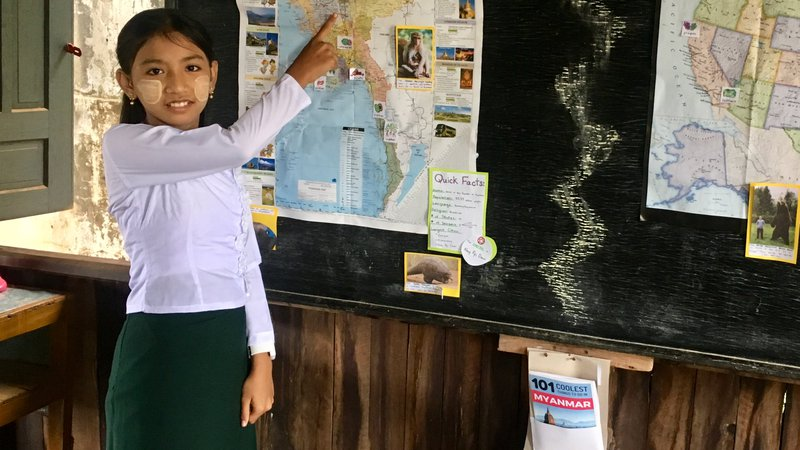 A girl stands and smiles while pointing to a map of Myanmar.
