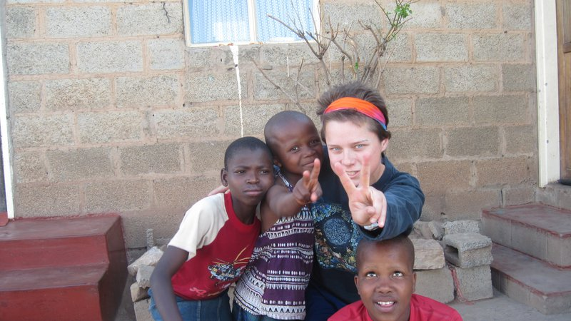 Young American woman poses playfully with three host sisters in Lesotho