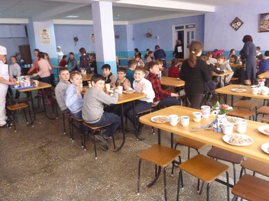 Children are sitting in the cafeteria waving to the camera