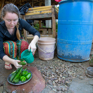 A Peace Corps Volunteer in Nepal squats on the ground, washing cucumbers and green peppers with water.
