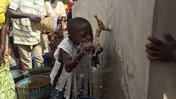 Feed the Future Water Project Ghana (Boy drinking  water)