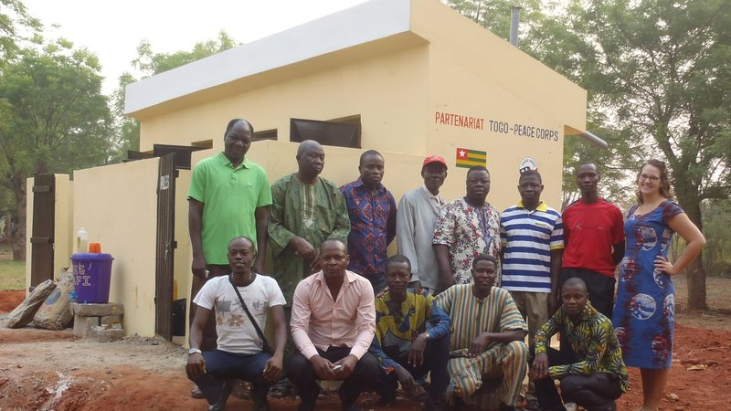 Togo: Community members pose with a Volunteer in front of the new latrines.