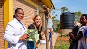 PCV Grace and her counterpart weigh a baby with the help of the baby's mother.
