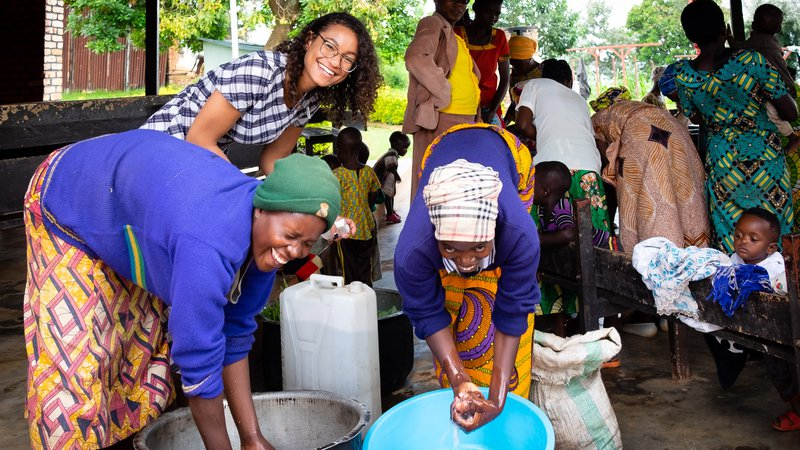 PCV Maya and two mothers wash their hands before preparing the group meal