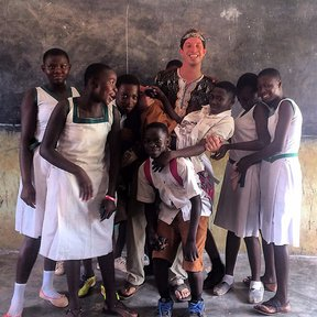 Peace Corps Volunteer standing in the classroom with students.