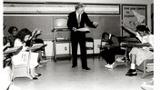 In a black and white photo, former Peace Corps Director Paul D. Coverdell stands in a classroom with young children, pointing