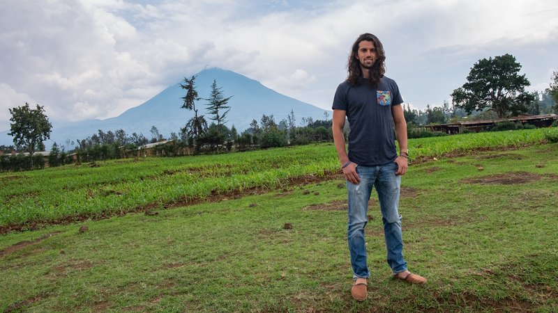 Andres poses outside with a volcano in the background