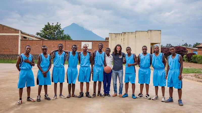 Andres poses with the basketball team at his school