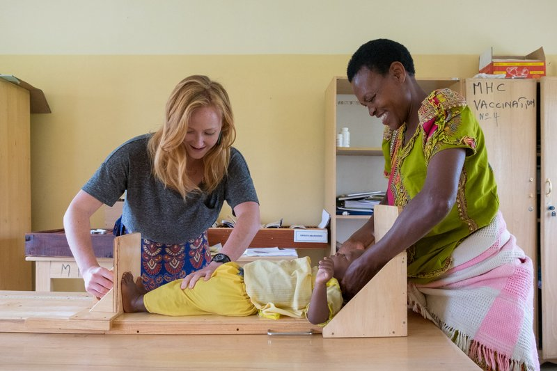 PCV Hannah with a mother measuring the height of the mother's child
