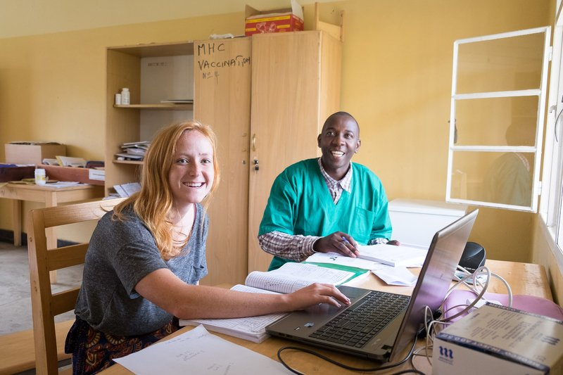 PCV Hannah with her counterpart at a table reviewing health data