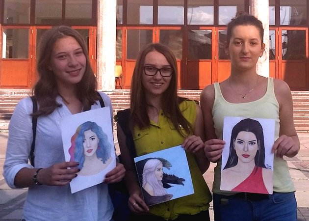 Three young women holding self-portrait paintings.