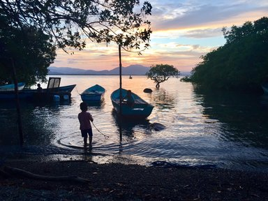 Two of our young neighbors play in their family's boat as the sun sets over the Guanacaste mountains.