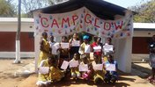 A Peace Corps Volunteer stands proudly with her Camp Glow participants under a banner.