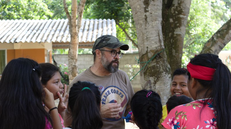 Hispanic male volunteer with beard talks with group of Ecuadorian students outside by a tree