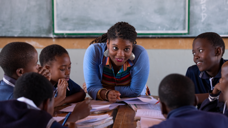 A Peace Corps Volunteer in South Africa leans over the front of a table, smiling as she talks to her young students.