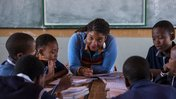 A black, female American teacher leans over a desk to work with young, teenage students in uniform in South Africa