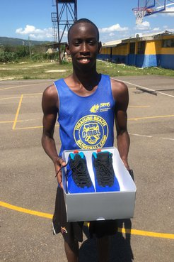 A Jamaican basketball player holds a box of shoes open on a basketball court.