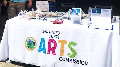 A booth at an art fair with brightly colored letters on a white tablecloth that reads San Mateo Arts and a white man in back