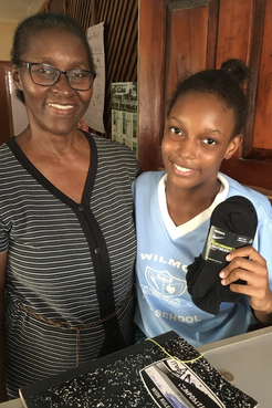 A Jamaican principal and her student holding up a pair of socks donated.