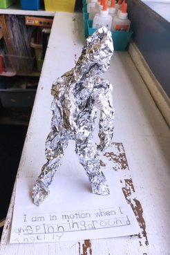 A close up of a foil sculpture that looks like a lumpy man made by a Jamaican primary school student on top of a table