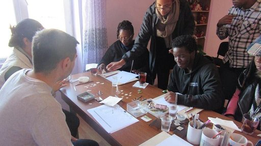Some out-of-town visitors and Peace Corps Volunteers learn how to make enamel jewelry during a workshop.