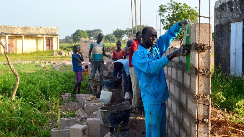 The head mason, Mortalla Diop, constructing the wall.jpg