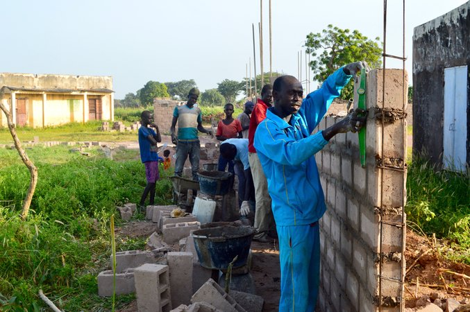 The head mason, Mortalla Diop, constructing the wall.jpg