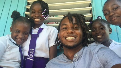 Male Trinidadian Teacher with dreads smiling beside Jamaican primary school students