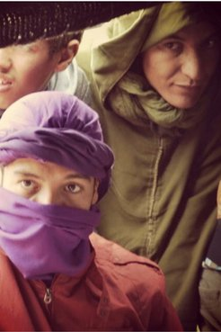 Two men, one in a raincoat and the other in a purple face covering, look at the camera while one looks away.
