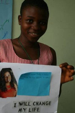 A student holding up art work.