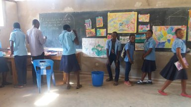 Students in blue uniforms stand at the front of the room looking at their paintings displayed on the black board