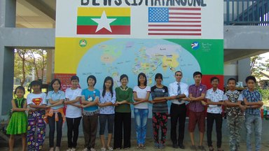 Teachers and students stand and link arms in front of a large, painted world map.