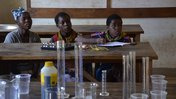 Three Malawian girls learn Chemistry at a STEM camp