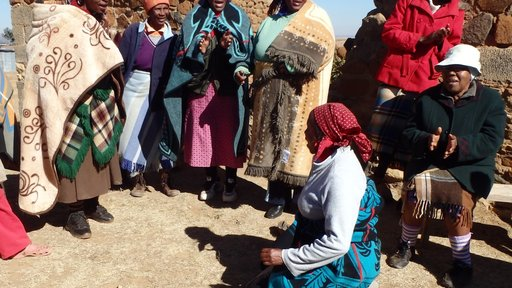 Women wearing all types of blankets for a community meeting..