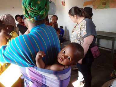 Waiting to be weighed at the outreach clinic, this baby stays warm despite the winter chill.