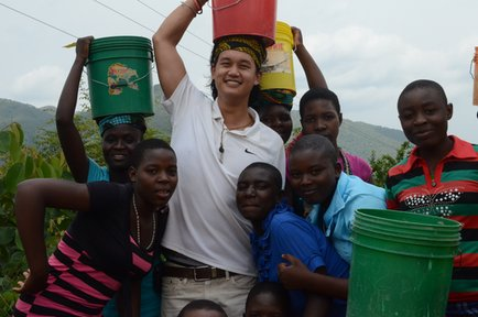 Education Volunteer Andrew carries water on his head with some students.