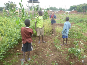 Peace Corps Volunteer Genevieve James teaches students how to collect seeds to plant next year.