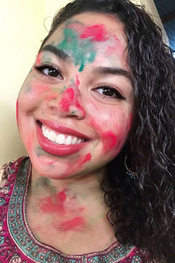 Headshot of smiling girl with face covered in colored powder