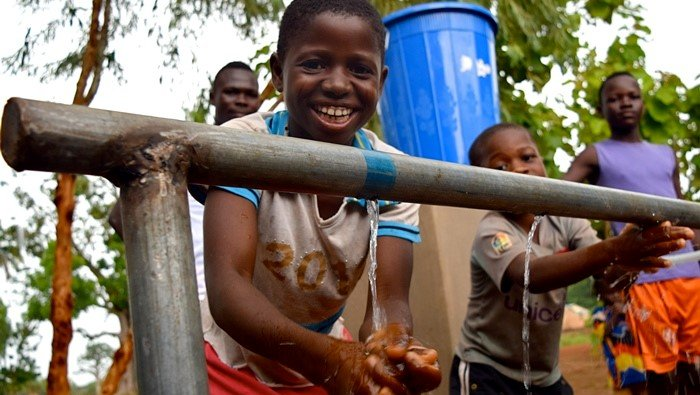 Young students happily use a handwashing station installed at their middle school.