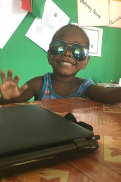 A child standing near a teachers desk with sunglasses on smiling.