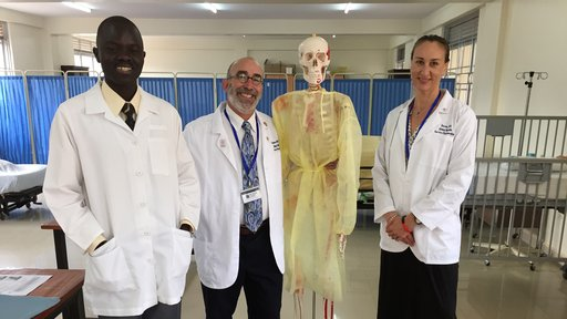 Global Health Service Partnership Volunteers and a faculty member of the nursing department, dressed in lab coast, stand next to a skeleton.